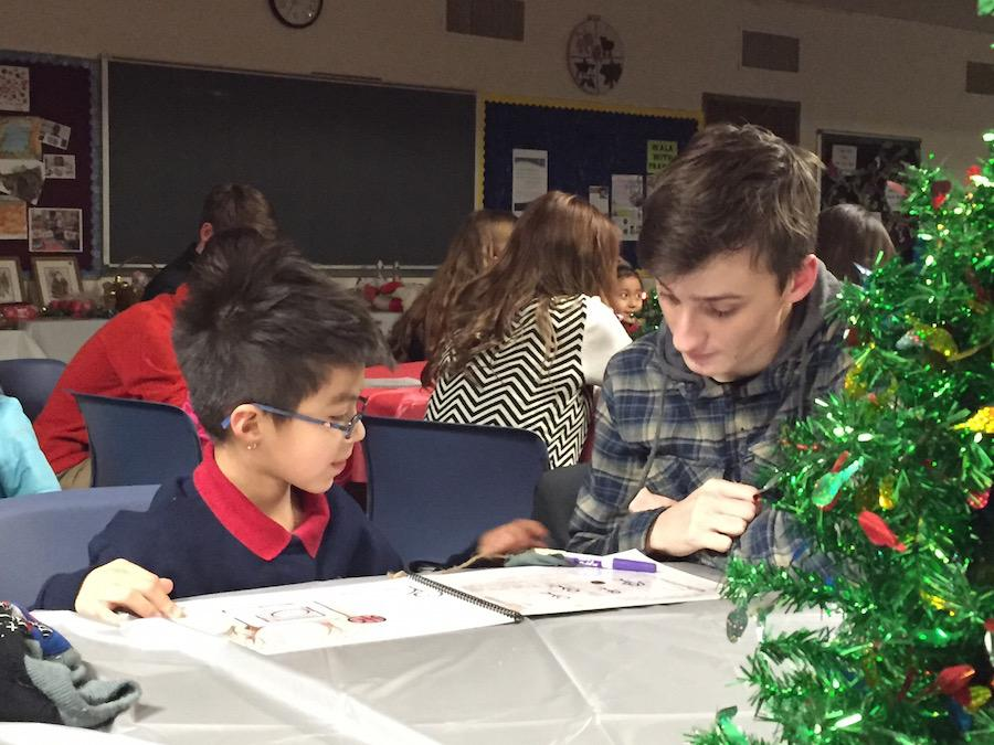 Junior Chase Mouser reads his original story with a student at Risen Christ.