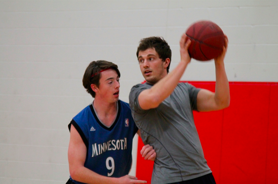 Junior Colin Segner shoves PE teacher Mr. Logan Radle during a game of intramural basketball. Radle also plays for the Minnesota Sting, a semi-pro football team that practices in Woodbury.