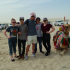 The victorious DI team poses in the Qatari desert next to a camel.
