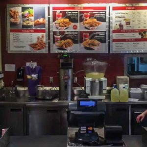 Raising Cane's counter seldom seen without a line of customers and cashiers frantically taking orders.