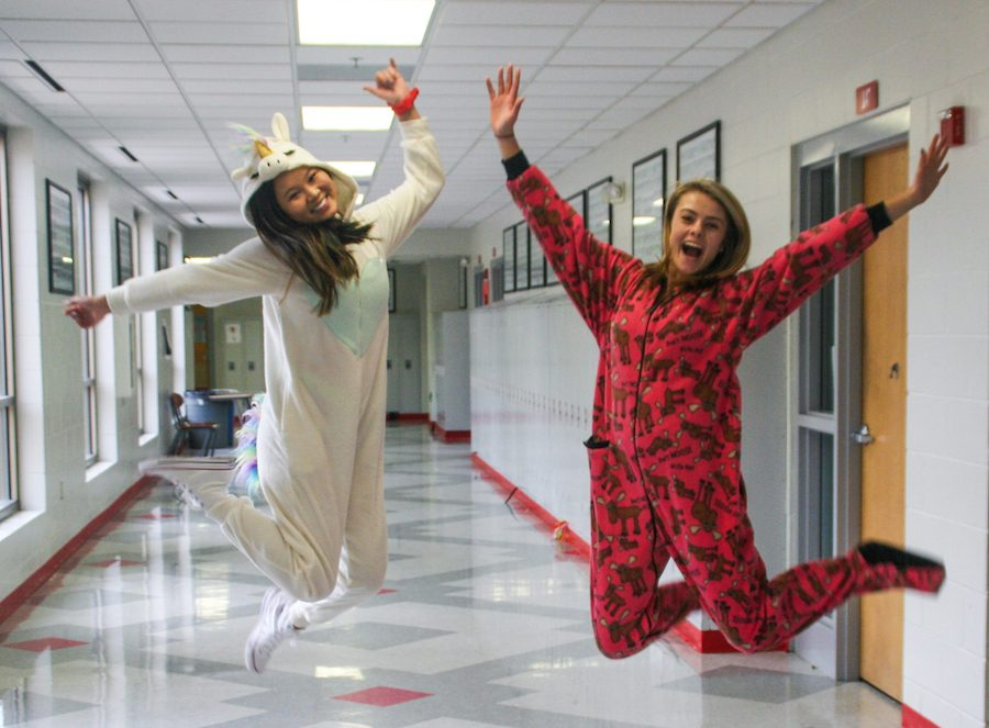 """Kathryn Hansen and Natalie Kroll jump for joy in their onesies. Tuesday was declared by the National Catholic Educational Association as a day for """"Celebrating your Students,"""" and BSM interpreted this by giving students the gift of comfort."""