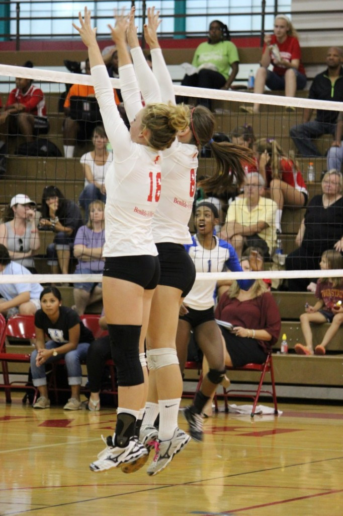 Two girls' volleyball players set up to block a play by the Hopkins Royals in their first home game on September 10.