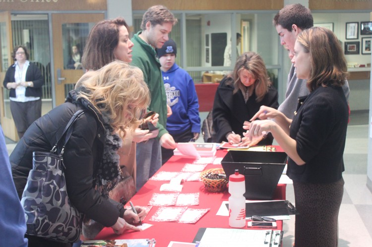 Prospective students and parents sign in for an open house.