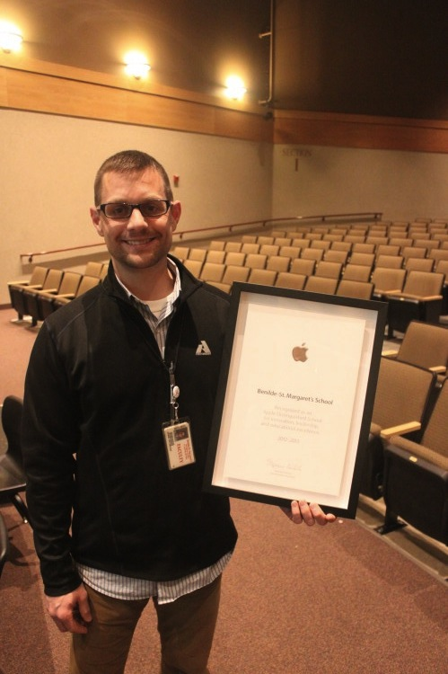 Technology Integration Assistant Mr. Dan Sylvester holds the Apple Distinguished School Award, presented to BSM this morning.