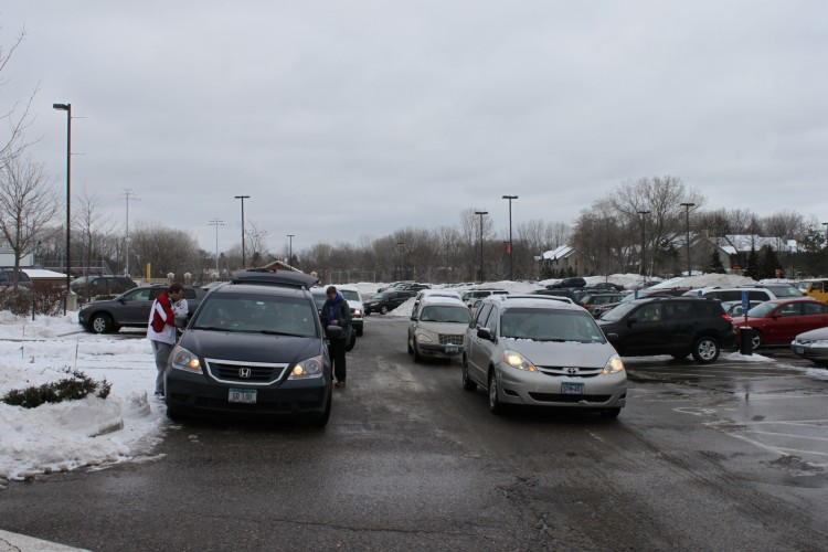 Snow+piles+in+the+parking+lot+are+plowed+to+make+way+for+parents+and+students+who+trek+to+school+despite+the+weather.+