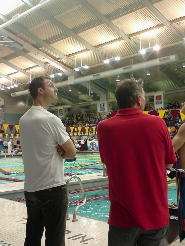 Head Coach Damon Carrison (left) and assistant coach Jon Weidenbacher (right) check out the scoreboard as Roe and Johnson race at State.