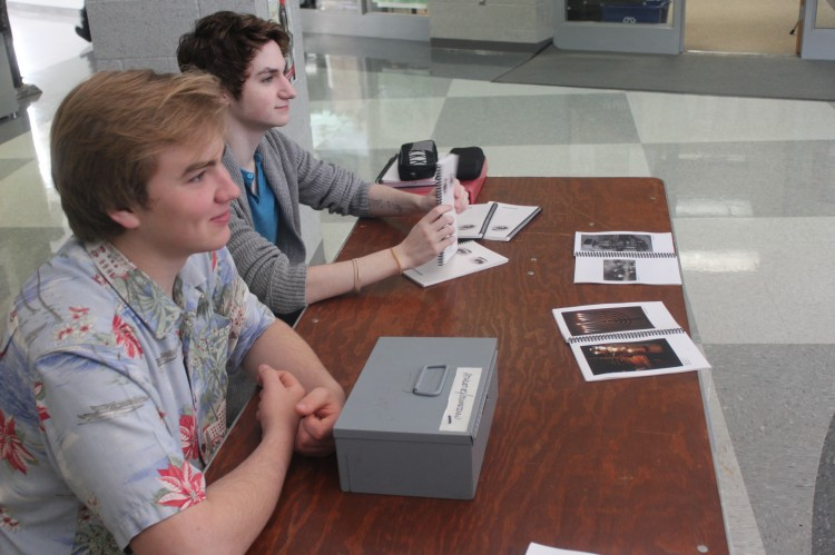Seniors Archie Boyle and Ben Clark sell Apotheosis magazines in the main lobby before school.