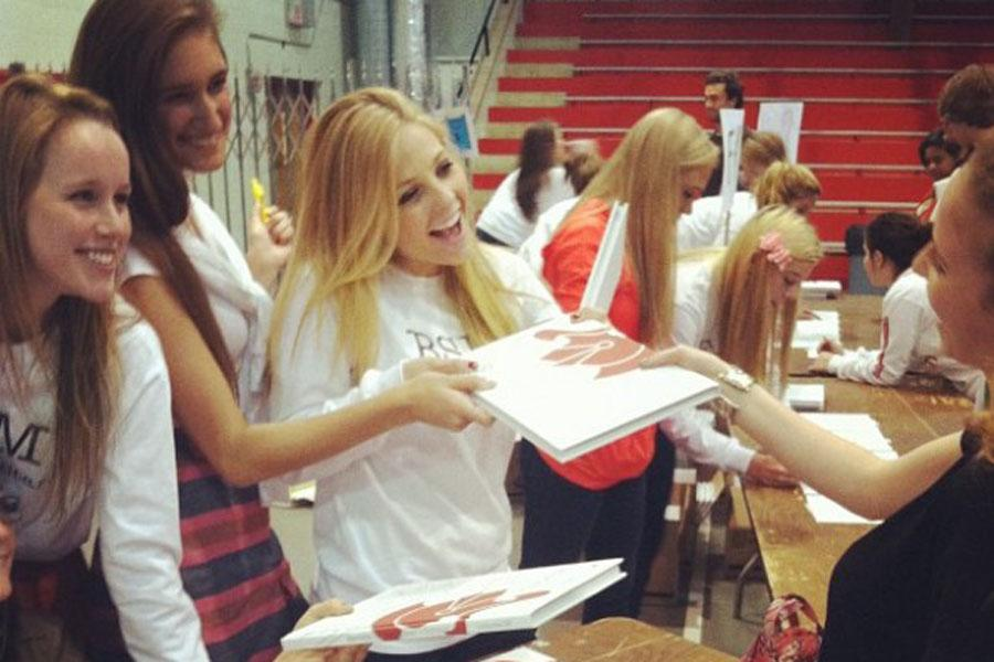 Sangraal editor-in-chief Eleanor Raether and seniors Abby Deutz and Abby Dryer hand out yearbooks.