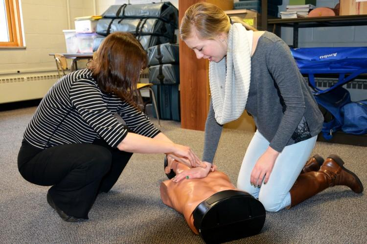 Health+teacher+Ms.+Alisa+may+helps+freshman+Madison+Semler+with+the+correct+procedure+for+chest+compressions.+
