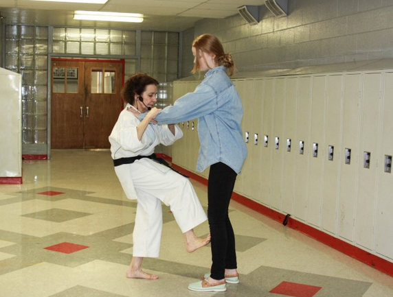 Freshman Claire Alme is instructed on how to properly defend herself by presenter Mary Brandl. The Black Belt instructor taught willing students how to spring into action while in dangerous situations.