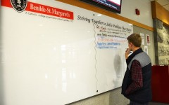 Senior Parker Breza adds problems that he believes matters to the whiteboard recently added to the lobby.