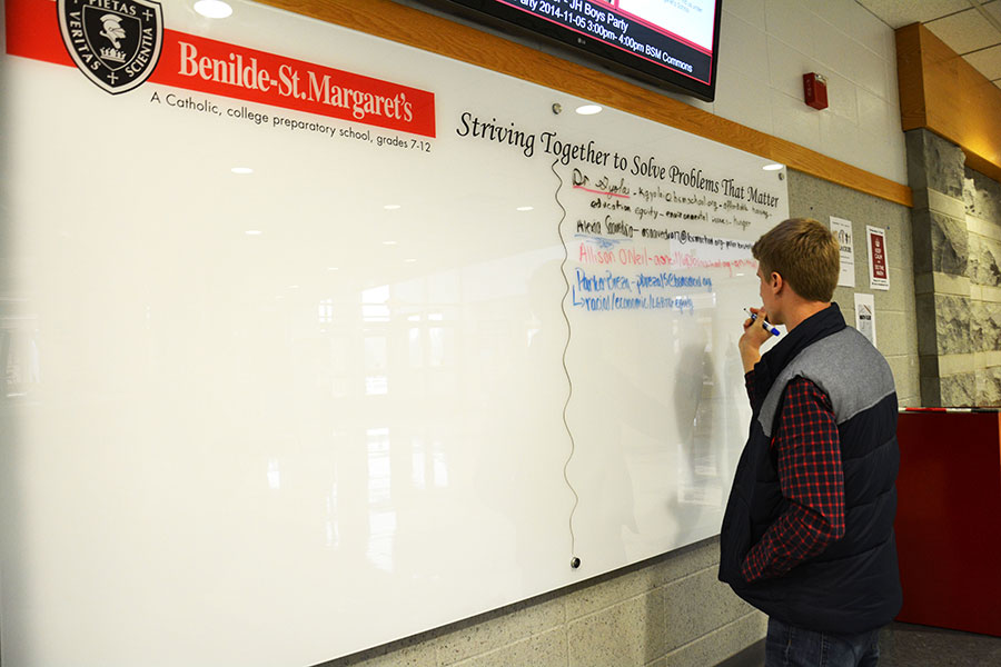 Senior+Parker+Breza+adds+problems+that+he+believes+matters+to+the+whiteboard+recently+added+to+the+lobby.+