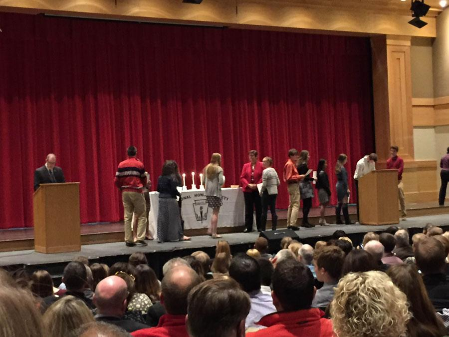 NHS inductees sign the official NHS ledger and receive their certificates.