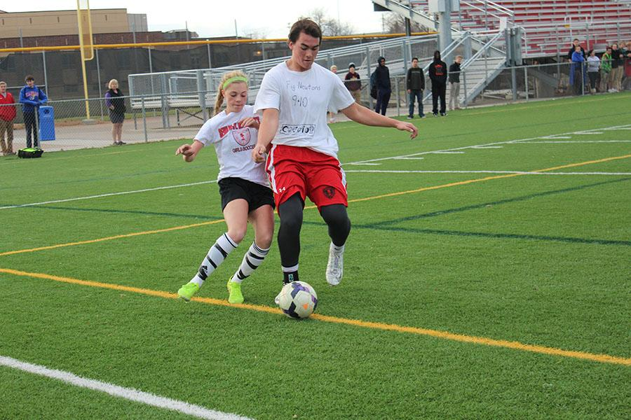 The girls' soccer team fought hard against the boy's football team and prevailed by a 3-1 margin.
