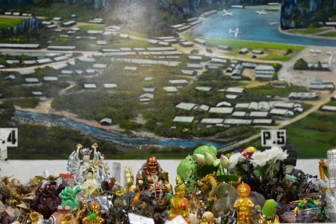 A Mural of a refugee camp is painted behind figurines for purchase at the Hmong Cultural Center.