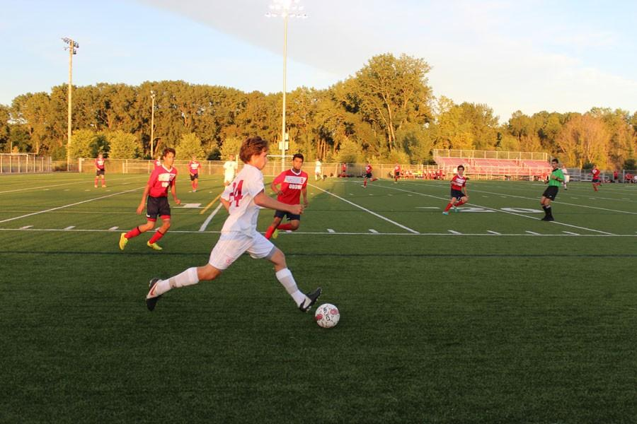 Senior captain Griffin Ehlen dribbles the ball upfield in a home game against Orono last season.