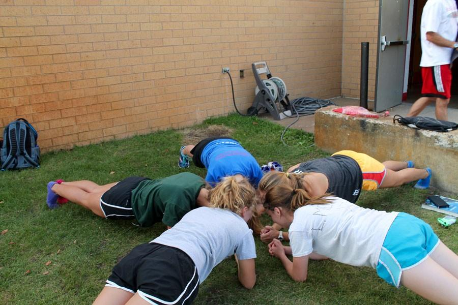 The+girls+cross+country+works+on+their+cores+by+doing+planks+after+a+recent+practice.