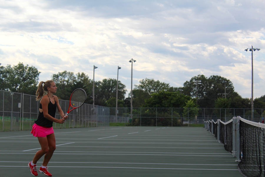 Taylor McLeod, who has been on the varsity tennis team since 7th grade, is getting ready to return a serve.