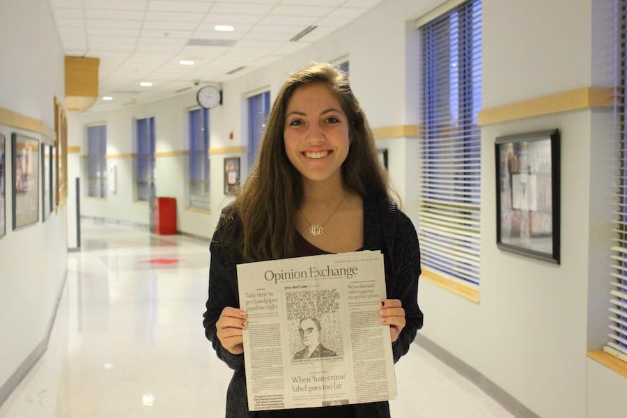 Sophomore+Anna+Carr+poses+with+her+article+published+in+the+Star+Tribune.+