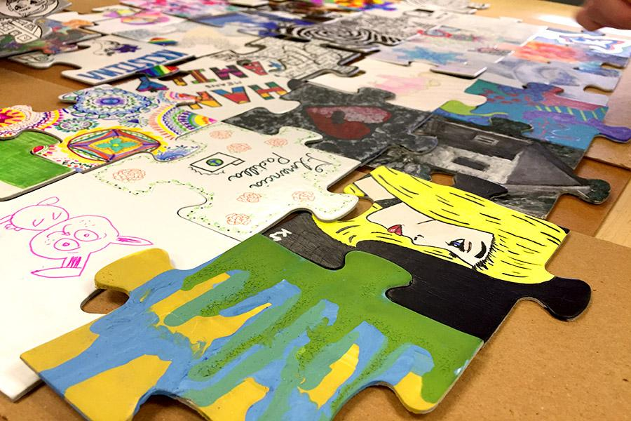 Puzzle pieces' mediums varied from acrylic paint to markers, photos, fabric, or a combination of materials.