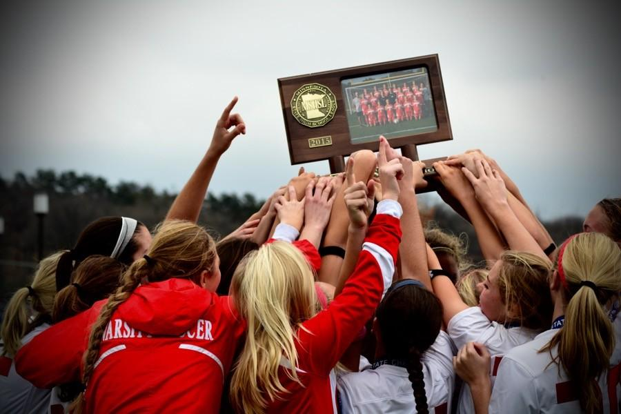 The+girls+proudly+hoist+the+State+Championship+trophy+for+the+third+time+in+the+last+four+years.