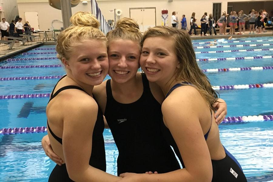 Grace Hedin, Gracey Scott, and Madison Semler pose during a break in the meet.