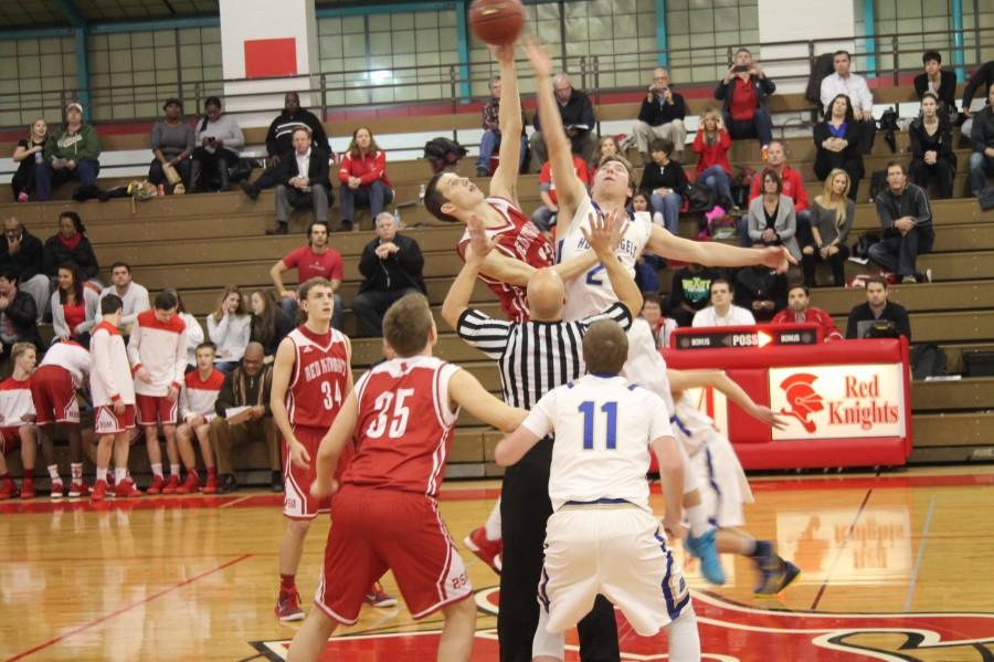 Senior captain Eli Cave asserts his will on the opening tip off in a game that the Red Knights beat Holy Angels by 40 points