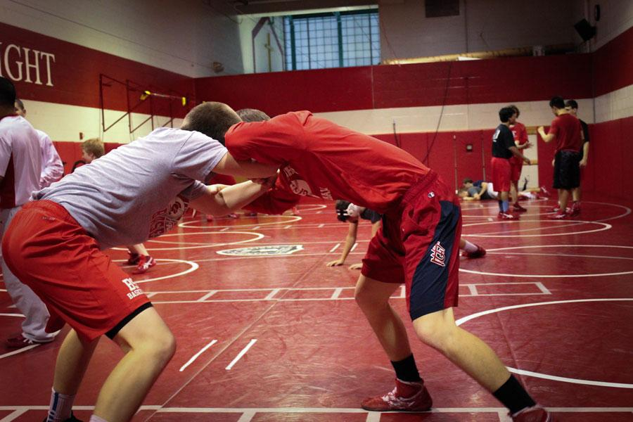 Two wrestlers are trying to take each other down in a strenuous recent practice.