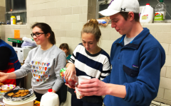 Juniors Macy Rooney, Molly Keady and Leo Driessen serve juice and treats at River Life's Men's Shelter.