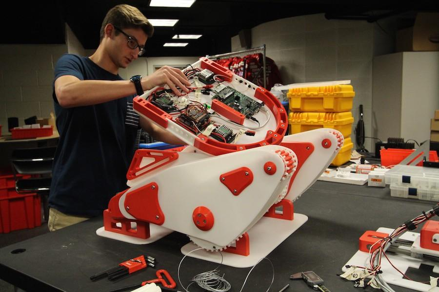 Engineering+III+student%2C+Bryan+Johnson%2C+works+on+the+robot+the+team+will+take+to+Germany.