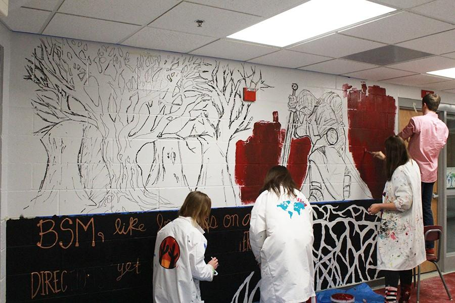Seven+seniors+in+NAHS+have+been+working+on+painting+the+mural+in+the+art+hallway+in+the+basement.+