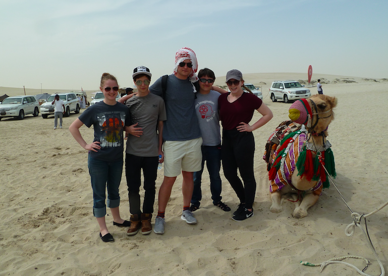 The+victorious+DI+team+poses+in+the+Qatari+desert+next+to+a+camel.