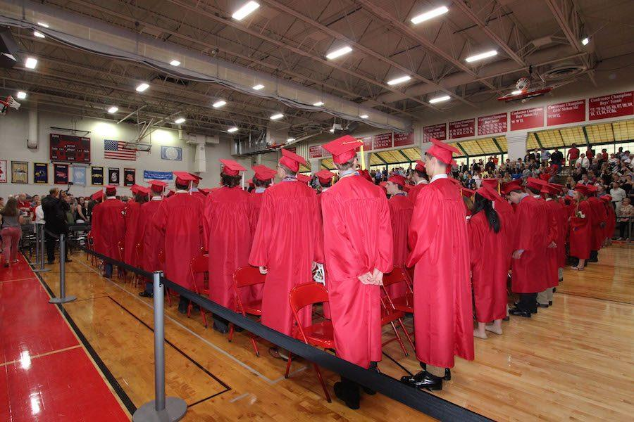 Graduates stand and face the teachers who have shaped who they are today.