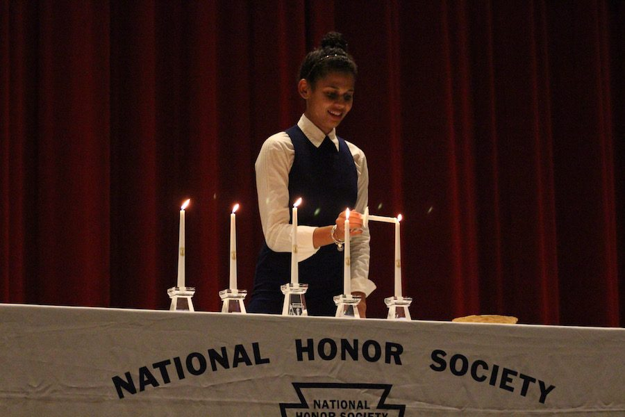 Senior Morgan Bettin-Coleman lights the Candle of Character, which is one of the four main pillars of NHS.