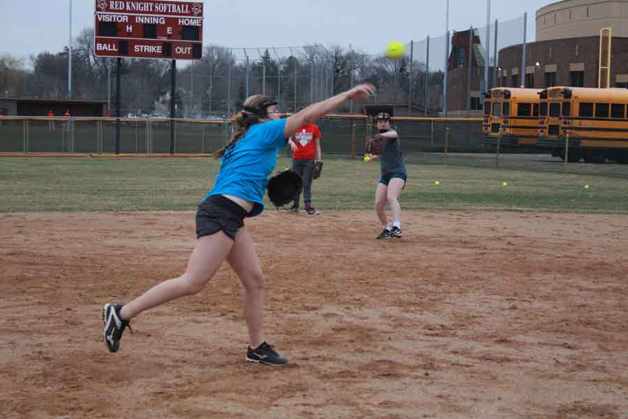 Junior Hattie Hoffman practices making a strong throw to first base in order to get the runner out.