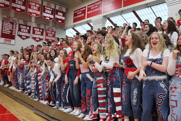 Senior girls cheer at a pep fest in their overalls.