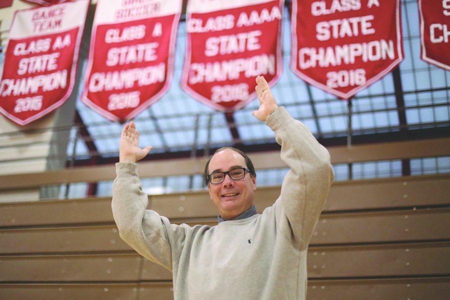 Teacher Mr. Kreiger stands under the 2016 BSM football championship banner.