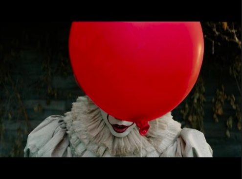 Pennywise the clown hides behind his signature red balloon.