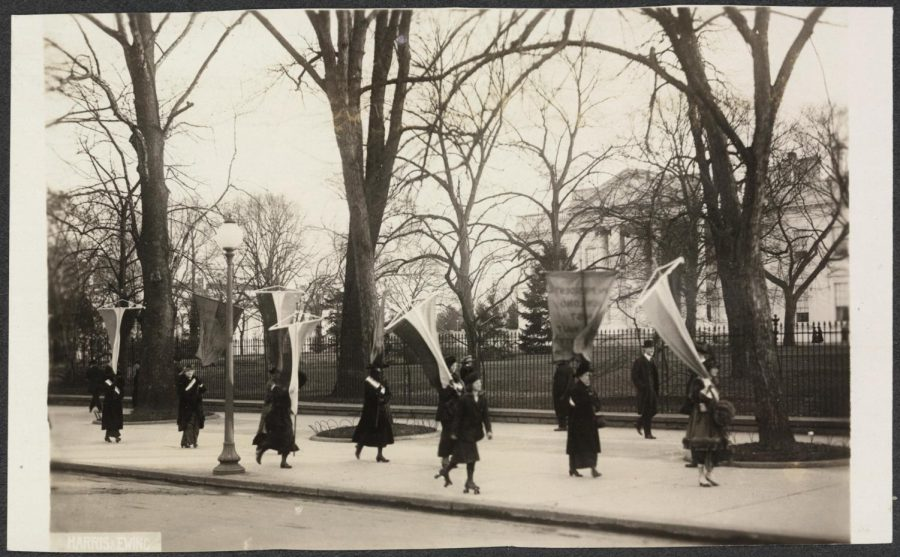 Suffragists picket the White House fence advocating for the right to vote.