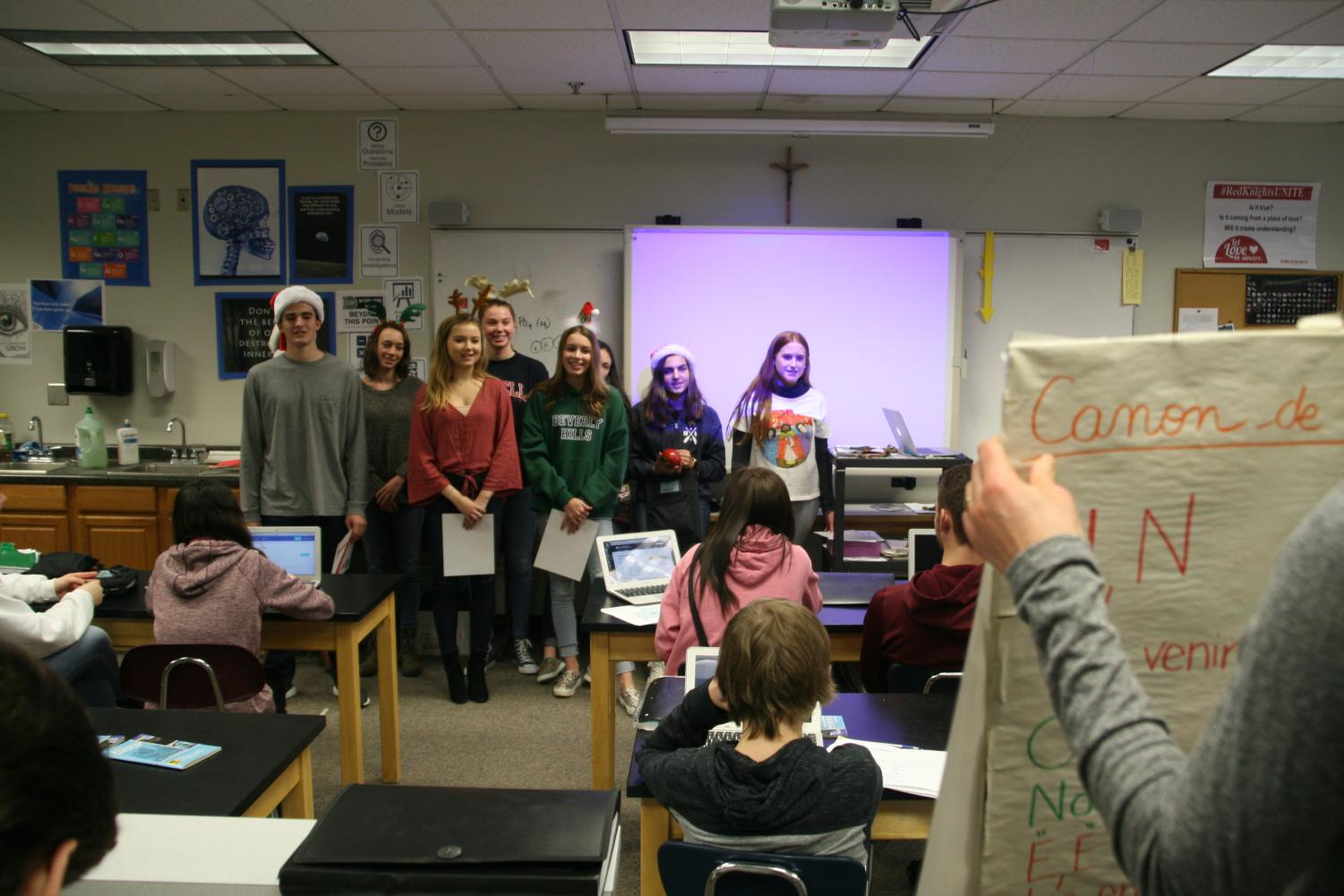 French students sang Christmas carols for a science class while their teacher held up posters to keep them from forgetting the words.