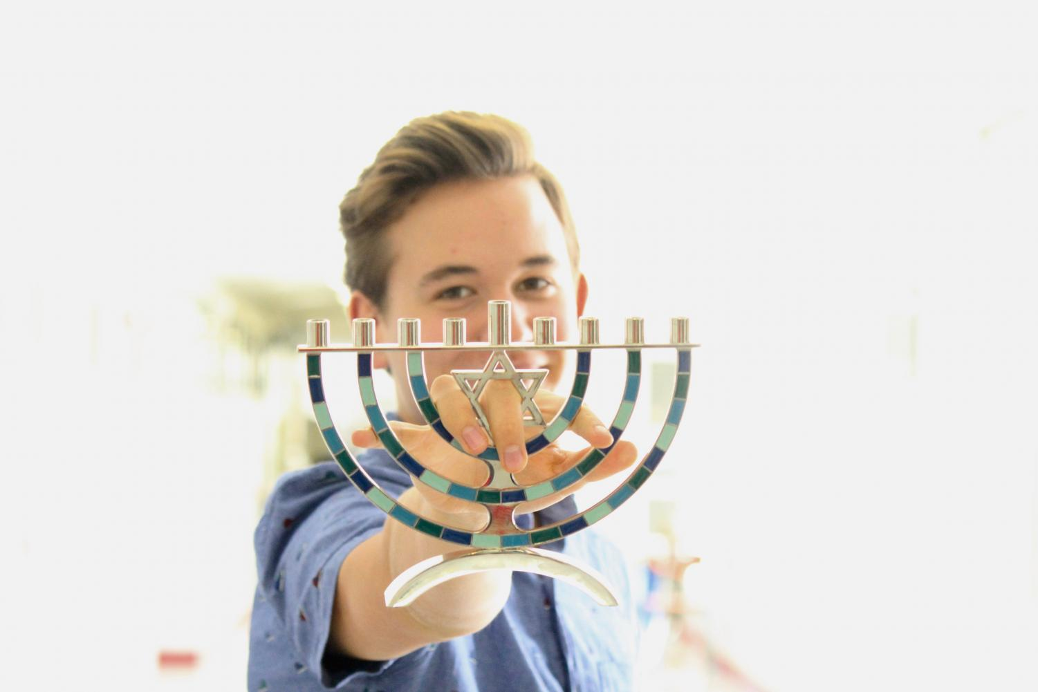 Noah Bridges eloquently clutches a menorah, which appears to be made of bathroom tile.