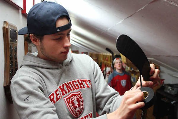 Senior boys' hockey captain Joe Collins tapes his stick before playing.