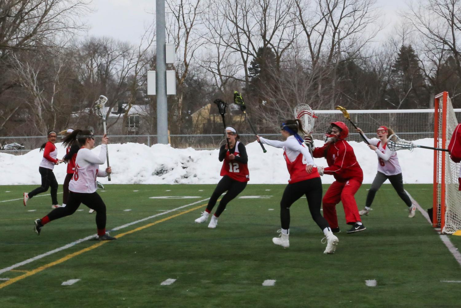 Despite the snow surrounding the field, members of the girls' lacrosse team get ready for the season. Personal workouts and captains' practices have been a part of their off-season preparation.