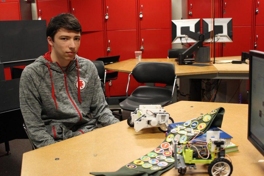 Brady Solomon shows off his robot and merit badges.