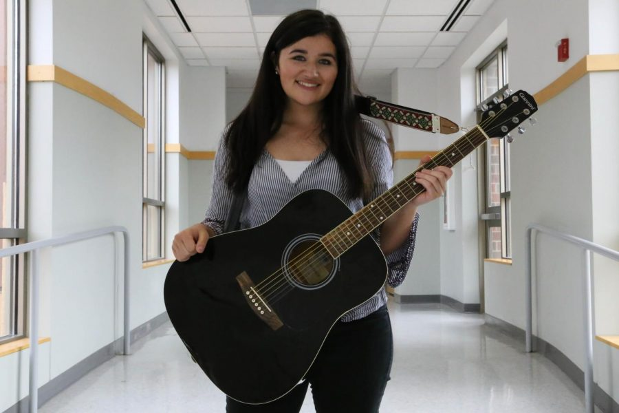 Senior Alyssa Brinza poses in the hallway with her guitar. When she first started playing, she used her mom's guitar which ended when she accidentally smashed it.