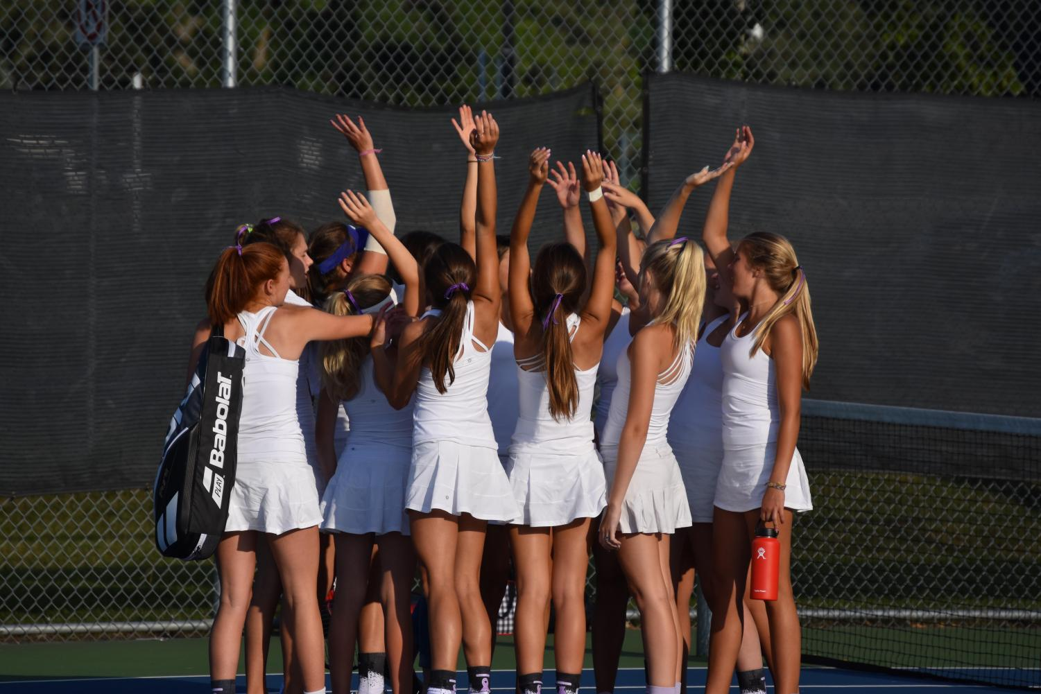 The BSM girls' tennis team celebrates after a win.