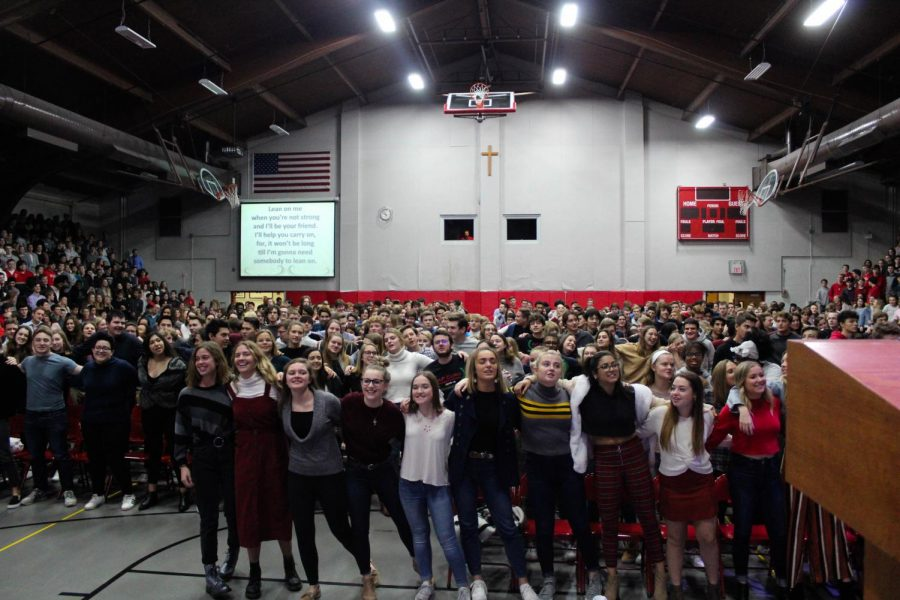 Students link arms swaying together in spirit of the song