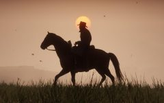 A cowboy riding his horse during the sunset