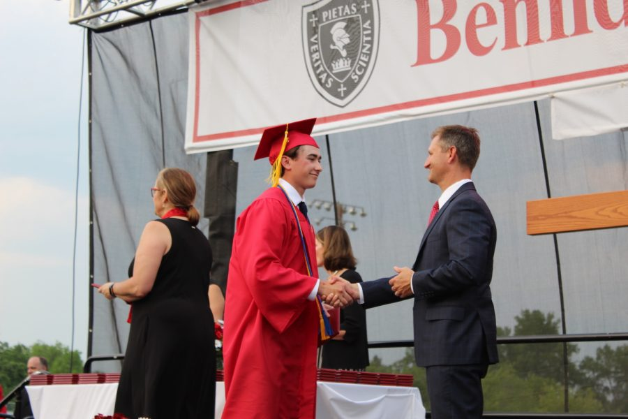 Dr. Adam Ehrmantraut shakes the hand of Nathan Anderson, the first graduate to receive his diploma.