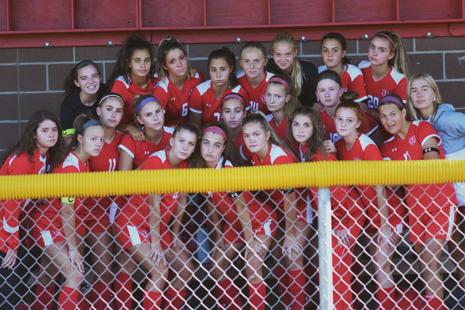Girls soccer team stand together, ready for their game.